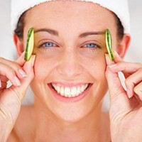 Closeup portrait of a smiling young woman holding cucumber slice